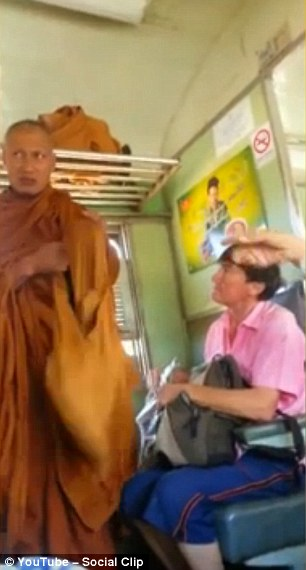 The monk looks to his right as a police officer arrives