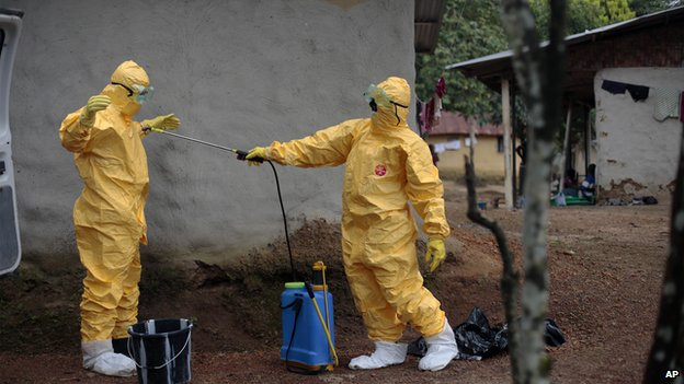 Medical workers disinfect each others suits in Liberia