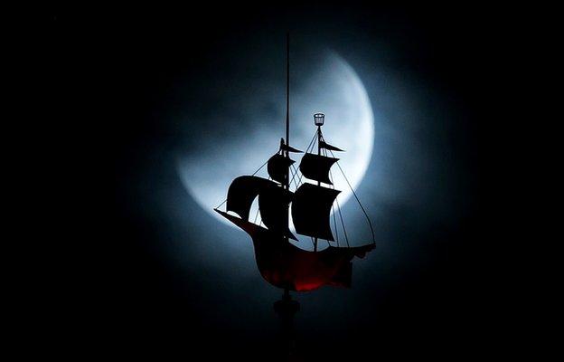Moon behind galleon weather vane