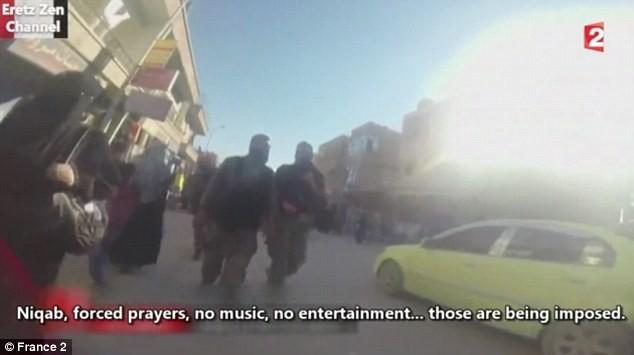 Những người đàn ông đeo súng đi khắp nơi trong thành phố. Ảnh: France 2