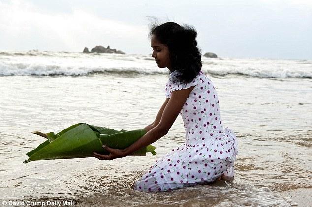 Tashmila Ushanthi, Sri Lanka – người may mắn sống sót sau thảm họa khốc liệt, bây giờ đã 20 tuổi đưa một chiếc bè làm bằng lá dừa thả xuống Ấn Độ Dương để tưởng nhớ các nạn nhân của thảm họa sóng thần cách đây mười năm.