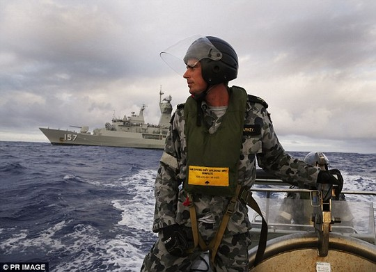 Leading Seaman, Boatswains Mate, William Sharkey searches for debris on a rigid hull inflatable boat in the Southern Indian Ocean in April. In the background is HMAS Perth, which was involved in the search