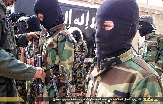 Một tướng lĩnh IS chỉ bảo cách dùng AK-47 để tấn công cho một cậu bé da trắng. Ảnh: Daily Mail