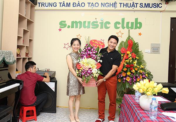 Giám đốc Ngô Thị Hải Yến đón nhận hoa chúc mừng của ca sĩ Đăng Thuật