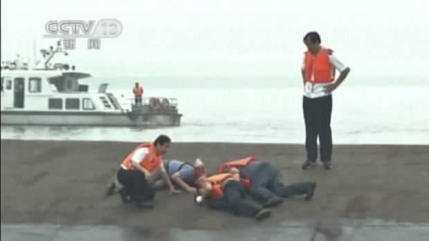 Rescue workers listen for a response to their tapping on the hull of a capsized ship on the Yangtze River.