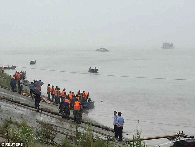 Emergency services and rescue patrol the river in a bid to find survivors amid the stormy weather conditions