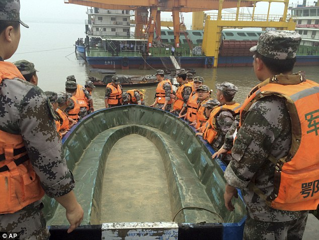 A group of rescue workers shift a boat down to the river bank to begin searching for survivors