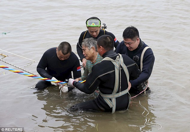 An elderly woman is pulled ashore after she was rescued from inside the hull of the partially submerged ship