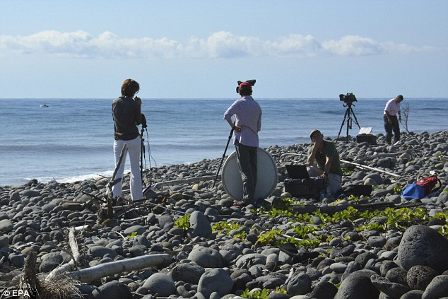 Television crews at work on Bois-Rouge beach on La Reunion where the debris from the as yet unidentified aircraft washed ashore