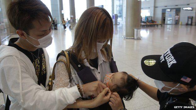 Tourists wear masks as a precaution against the Mers virus at the Incheon International Airport on 6 June
