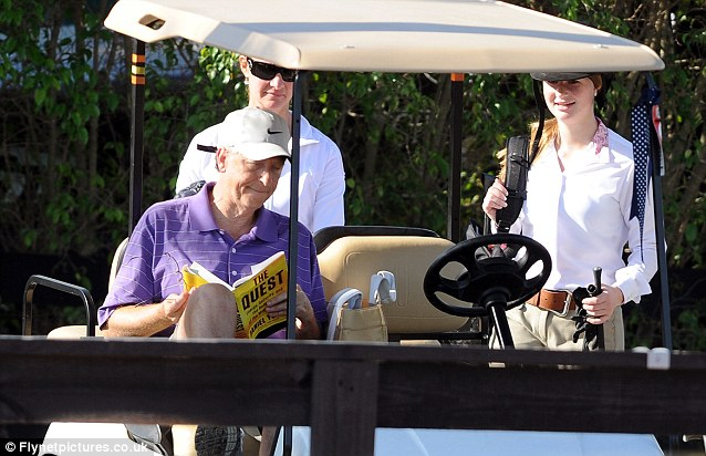 Distracted: Billionaire Bill Gates takes a break from the horse riding activities to read The Quest - a book about global energy and its role in geopolitical and economic change