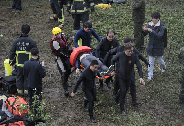 Emergency personnel carry the body of a passenger extracted from the commercial plane after it crashed