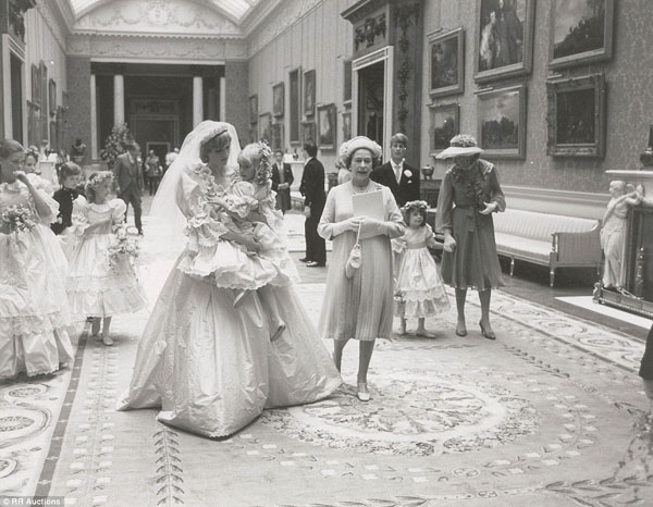 Whispering words of encouragement to her five-year-old bridesmaid, Diana, Princess of Wales, looks resplendent in her wedding dress as she carries the young girl through the grand rooms of Buckingham Palace.