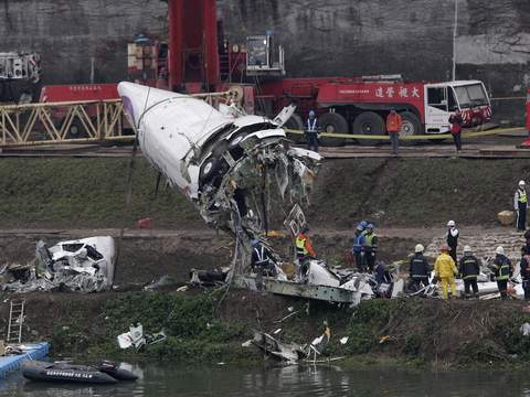 Emergency teams remove pieces of wreckage at the site of the crashed TransAsia Airways plane Flight GE235 in New Taipei City