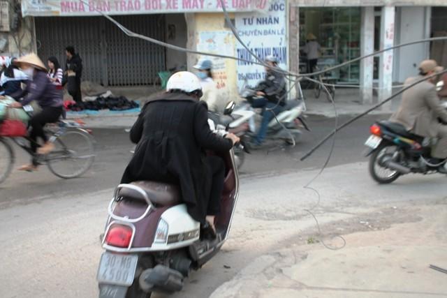 Người phụ nữ này phải cúi người để tránh dây điện thòng lọng xuống đường ở cầu Định Công (Hà Nội). (Ảnh: Báo Dân sinh)