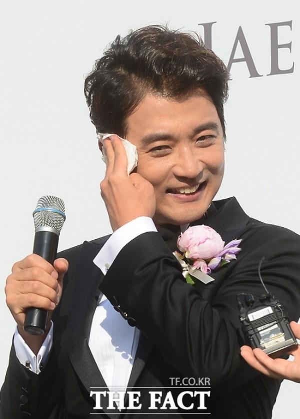 """Do thời tiết khá khó chịu nên Ahn Jae Wook liên tục toát mồ hôi và phải lau mặt. Anh cười chia sẻ: """"Chú rể không hề trang điểm nên không sợ son phấn trôi""""."""