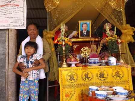Bà Quang và đứa cháu ngoại bên ban thờ người thân