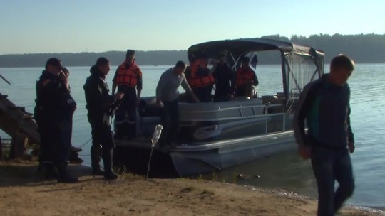 Đội cứu hộ tìm kiếm trên hồ chứa. Ảnh: RT
