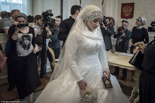 Not the happiest day of her life: Chechen teenager Kheda Goilabiyeva clutches a passport as she looks down despondently after being forced to marry an ally of Chechen strongman Ramzan Kadyrov who reportedly threatened to kidnap her if she and her parents refused to comply