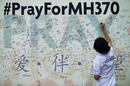 Cầu nguyện cho MH370. Ảnh: Rauters