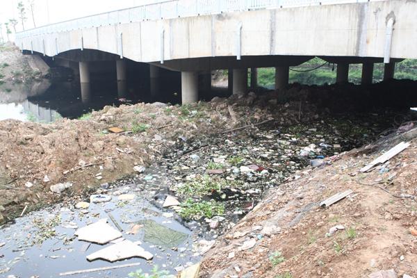 Đất đá lẫn rác ngập cả một khúc sông cạnh đường Tố Hữu.