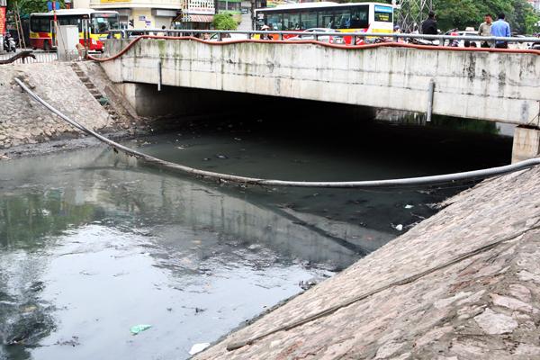 Một đoạn sông Kim Ngưu chảy qua cầu Lạc Trung chứa nhiều bùn rác dập dềnh trong nước.