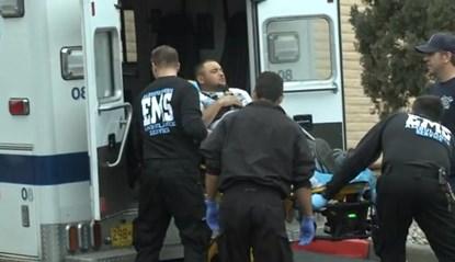 Anh Reynolds được đưa ra xe cứu thương sau khi bị bắn