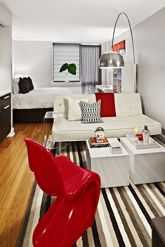 Mẫu căn hộ này được phân chia không gian giữa bàn tiếp khách và giường ngủ bằng rèm màu ghi rất khéo léo. Như với các căn hộ nhỏ khác, căn hộ này cũng được sử dụng tường trắng và đồ nội thất màu sáng để tạo cảm giác rộng rãi và thoáng mát về mặt thị giác. Điểm nhấn của căn hộ là chiếc ghế màu đỏ phối cùng với những đồ decor nhỏ khác tạo nên một không gian hoàn hảo cho căn hộ.