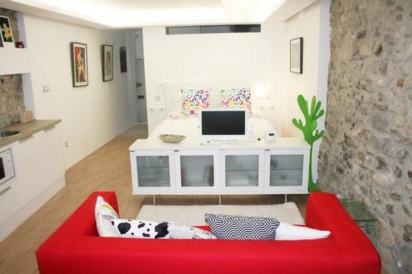 Giường ngủ được ngăn cách với khu vực tiếp khách bằng hệ kệ để tivi, tạo cảm giác mở nhưng vẫn có tính riêng tư giữa hai khu vực.