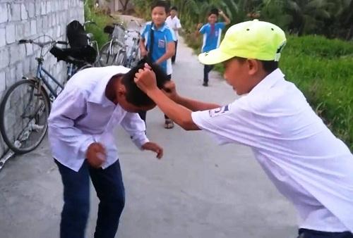 """Học sinh lớp 7 ở Hải Dương bị nhóm bạn học đánh """"hội đồng"""" chỉ vì không chịu """"nộp tô""""( ảnh cắt từ clip)."""