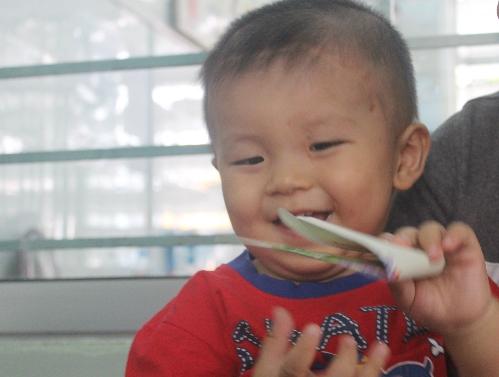 Cậu bé mọc được 10 chiếc răng sữa, thích thú cười đùa cùng mọi người. Ảnh: Lê Phương.