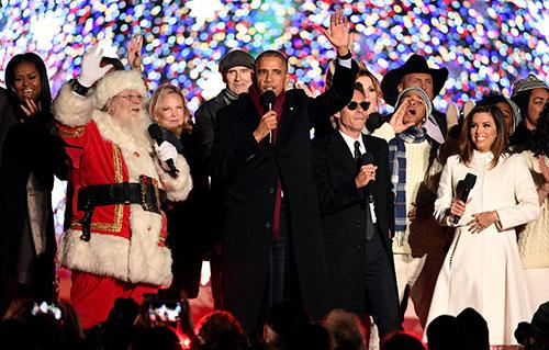 Ông Obama hát cùng dàn nghệ sĩ và ông già Noel trong buổi lễ. Ảnh: Reuters