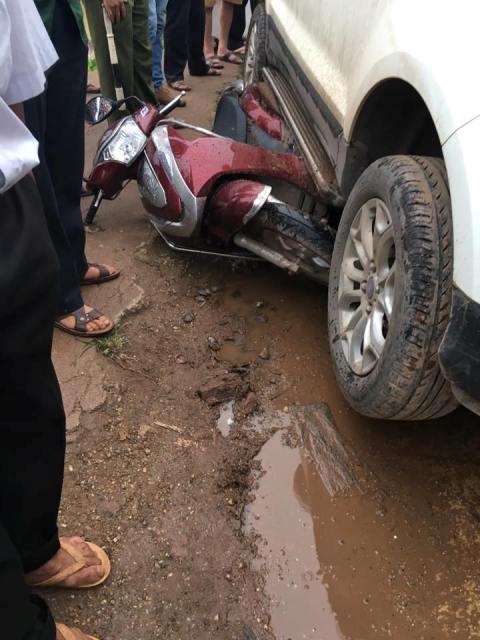 Chiếc xe máy bị mắc kẹt trong gầm xe ô tô sau vụ tai nạn. Ảnh: Đức Việt