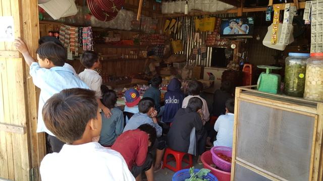 Những em học sinh trường bán trú tỏ ra thích thú khi thấy tivi của một hàng tạp hóa cạnh trường chiếu phim. Ảnh: Cao Tuân