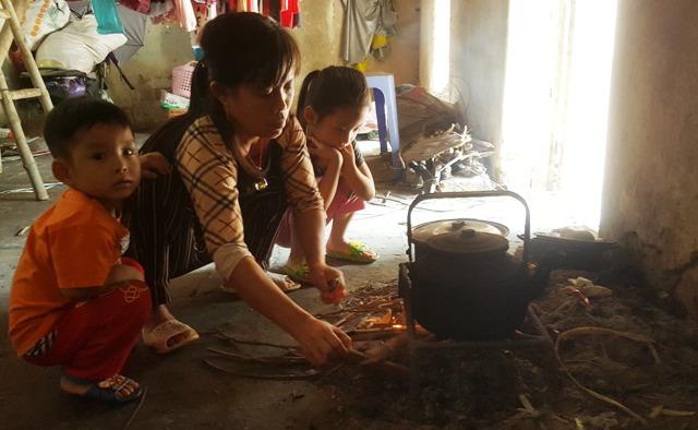 Bên góc bếp lụp xụp, chị Nguyễn Thị Thanh đang thổi cơm cho gia đình. Ảnh: Cao Tuân