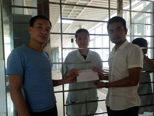 PV Cao Tuân, đại diện chuyên mục Vòng tay nhân ái - Báo Gia đình & Xã hội trao tiền của bạn đọc ủng hộ đến anh Nguyễn Văn Sỹ và chị Phạm Thị Lâm (bố mẹ bé Thế).