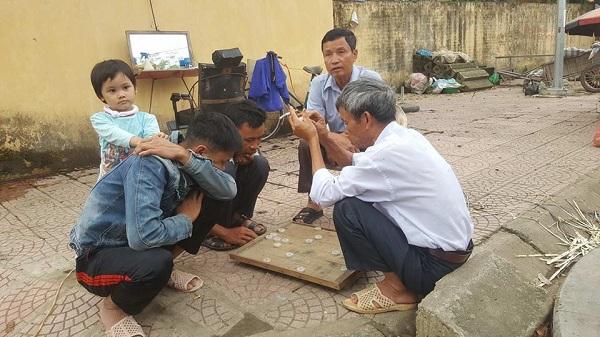 Một số người dân vui vẻ chơi cờ ven đường làng.