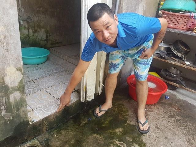 Anh Đặng Đình Đức chỉ vào khu vực nhà tắm nơi anh Đặng Đình Q. bị ngã đập đầu dẫn đến tử vong. Ảnh: PV