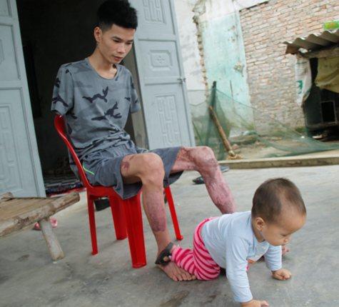 Anh Hải dùng chân để chơi đùa với con. Ảnh: V.Đồng
