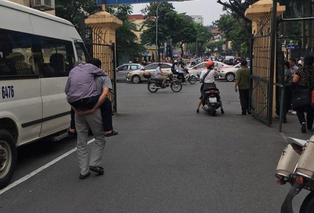 Con trai bị cáo Nguyễn Danh Vĩnh cõng bố rời khỏi phòng xét xử ra xe ô tô về nhà.