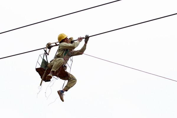 Công nhân Truyền tải điện Kon Tum đang vệ sinh cách điện tại vị trí 62 ĐZ 220 kV Kon Tum - Pleiku.