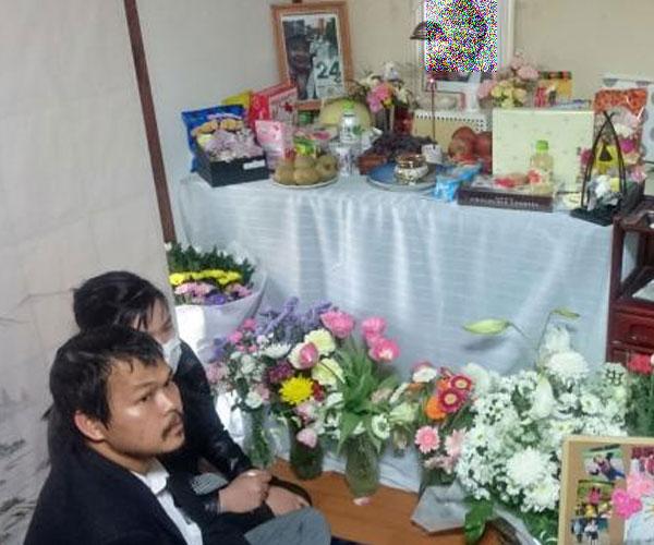 Bố mẹ bé gái người Việt xấu số ngồi bên ban thờ của con ở nơi sinh sống hiện tại.