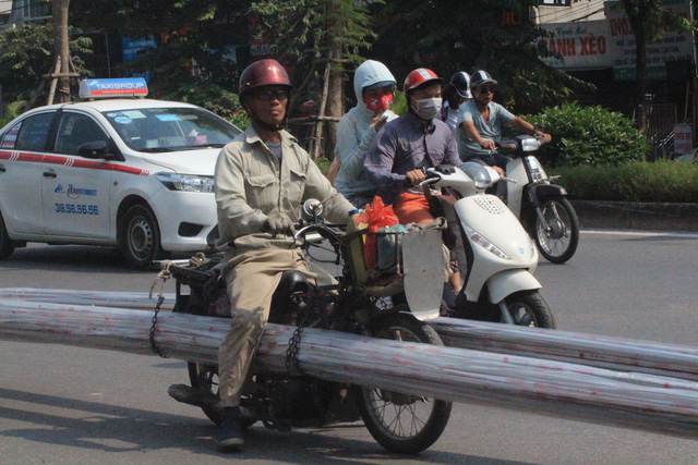 Xe máy cũ nát chở hàng cồng kềnh trên đường Đại Cồ Việt. Ảnh: HP