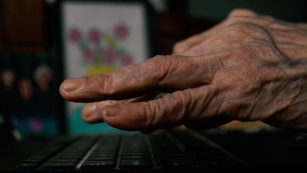 Những ngón tay của cụ nhẹ nhàng lướt bàn phím.