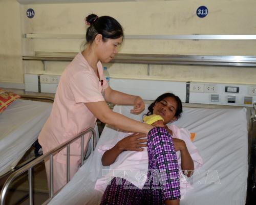 Điều dưỡng Nguyễn Thị Kim Long (trái) hướng dẫn sản phụ và người thân chăm sóc trẻ sinh non, nhẹ cân theo phương pháp chăm sóc bà mẹ Kangaroo.