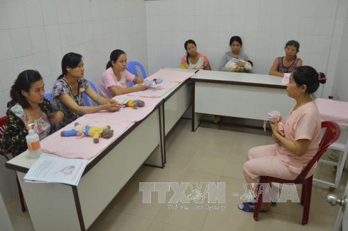 Điều dưỡng Nguyễn Thị Kim Long (phải) hướng dẫn sản phụ và người thân chăm sóc trẻ sinh non, nhẹ cân theo phương pháp chăm sóc bà mẹ Kangaroo.