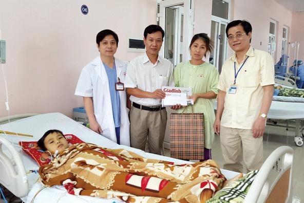 Ông Nguyễn Ngọc Đức – Phó TBT Báo GĐ&XH, ông Phạm Lương An, Phó Giám đốc Bệnh viện K (ngoài cùng bên phải) trao số tiền độc giả ủng hộ cho gia đình cháu Công. Ảnh: P.T