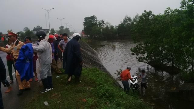 Người dân giúp đỡ hi mẹ con chị Anh vớt chiếc xe máy gặp nạn dưới vũng nước sâu. Ảnh: A.K