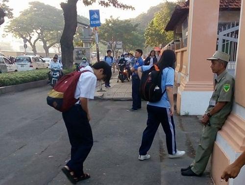 Học sinh lễ phép chào người đàn ông làm nhiệm vụ bảo vệ trước cổng trường.
