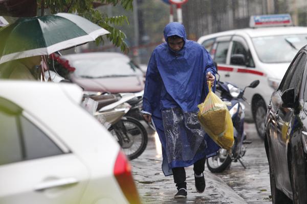 Cơn mua bất chợt chiều nay khiến cánh đàn ông phải đội mưa mua hoa.